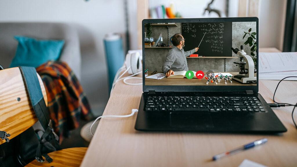 Op een tafel staat een opengeklapte laptop. Op het scherm is een man in beeld die met een stok op een krijtbord achter zich wijst. Voor hem ligt een boek, een microscoop.