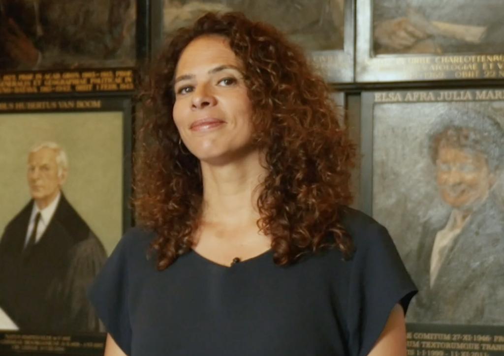 Nadira Saab kijkt glimlachend in de camera. Op de achtergrond zijn portretten te zien.