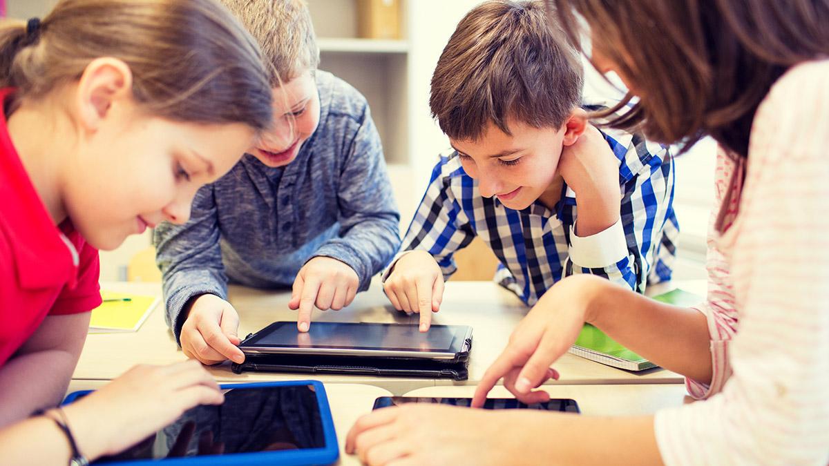 Vier leerlingen kijken op een iPad en tikken het scherm aan