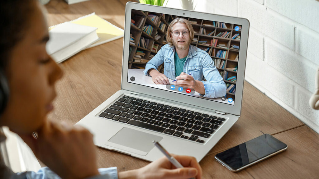 Een laptop staat op tafel en op het scherm is een blonde jongen met bril en baard te zien. Op de voorgrond is de zijkant van een donker meisje te zien, haar gezicht is meer wazig.