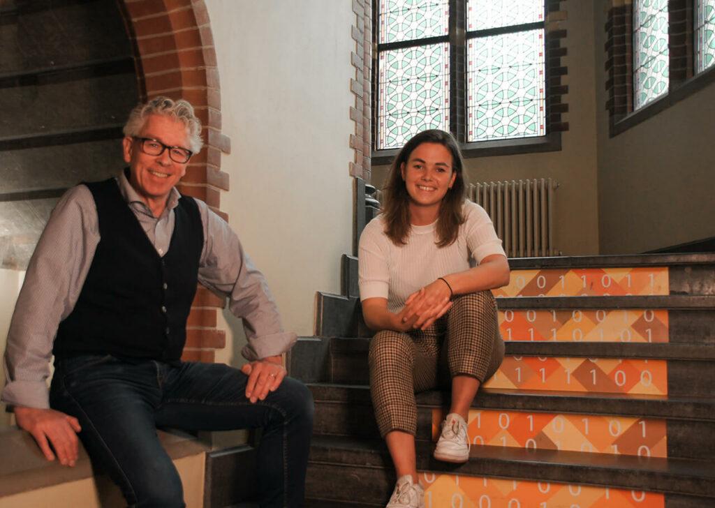 Practor Chris Holman en projectleider Marleen Blaauw zitten in een trappengang van het kasteel en ROC Noorderpoort. Zij kijken beide lachend in de camera.
