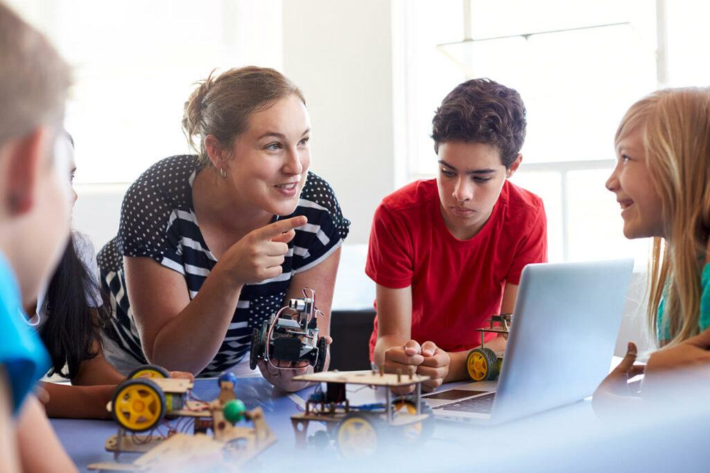 Een lerares heeft een technische auto in haar hand en wijst met haar vinger naar een leerling. Een jongen hangt tussen hun in op tafel en kijkt naar wat er op tafel ligt.
