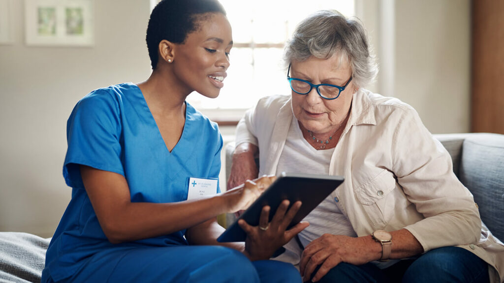 Een vrouw van de thuiszorg heeft een tablet in haar handen en helpt een oudere vrouw die naast haar zit