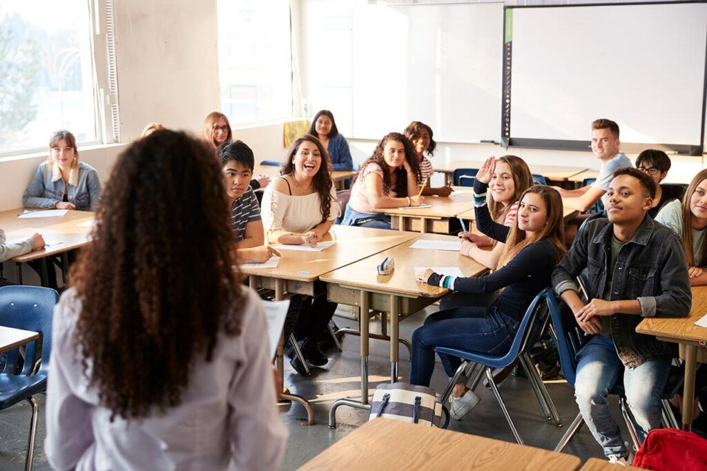 Leerlingen in een klas zitten aan hun tafels en kijken naar de juf voor de klas. Zij staat met haar gezicht naar de groep toe en met haar rug naar de kijker.