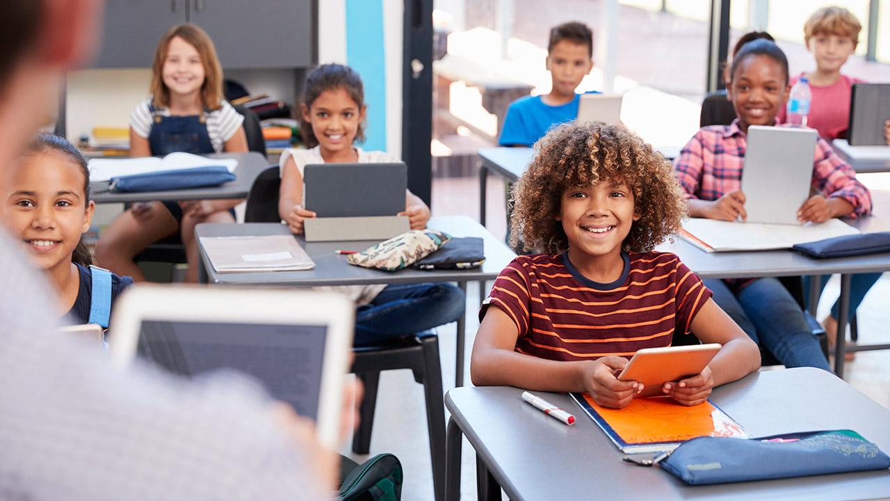 7 leerlingen zitten in de klas met een tablet voor zich en kijken lachend naar de leraar
