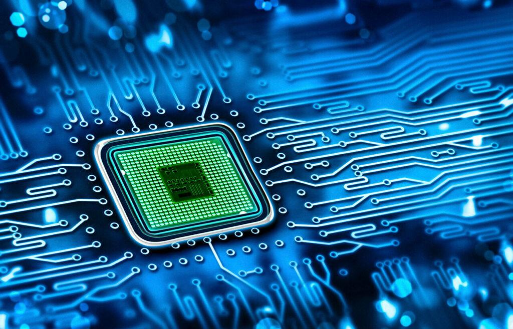Op de foto is een deel van een chip te zien die in elektronisch apparatuur zit. De chip is groen en de rest is blauw.