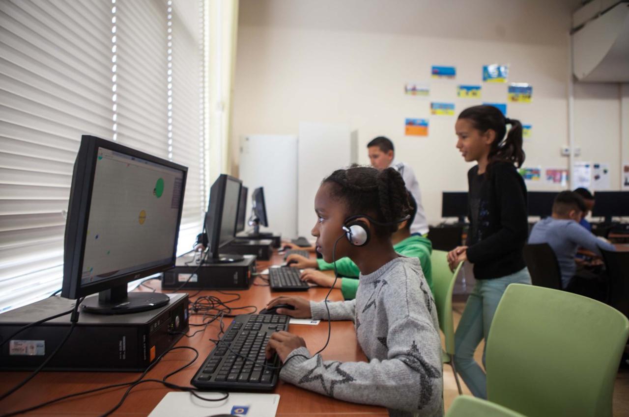 Een leerling werkt op een desktop op school en kan online veilig en snel bij de digitale leermiddelen