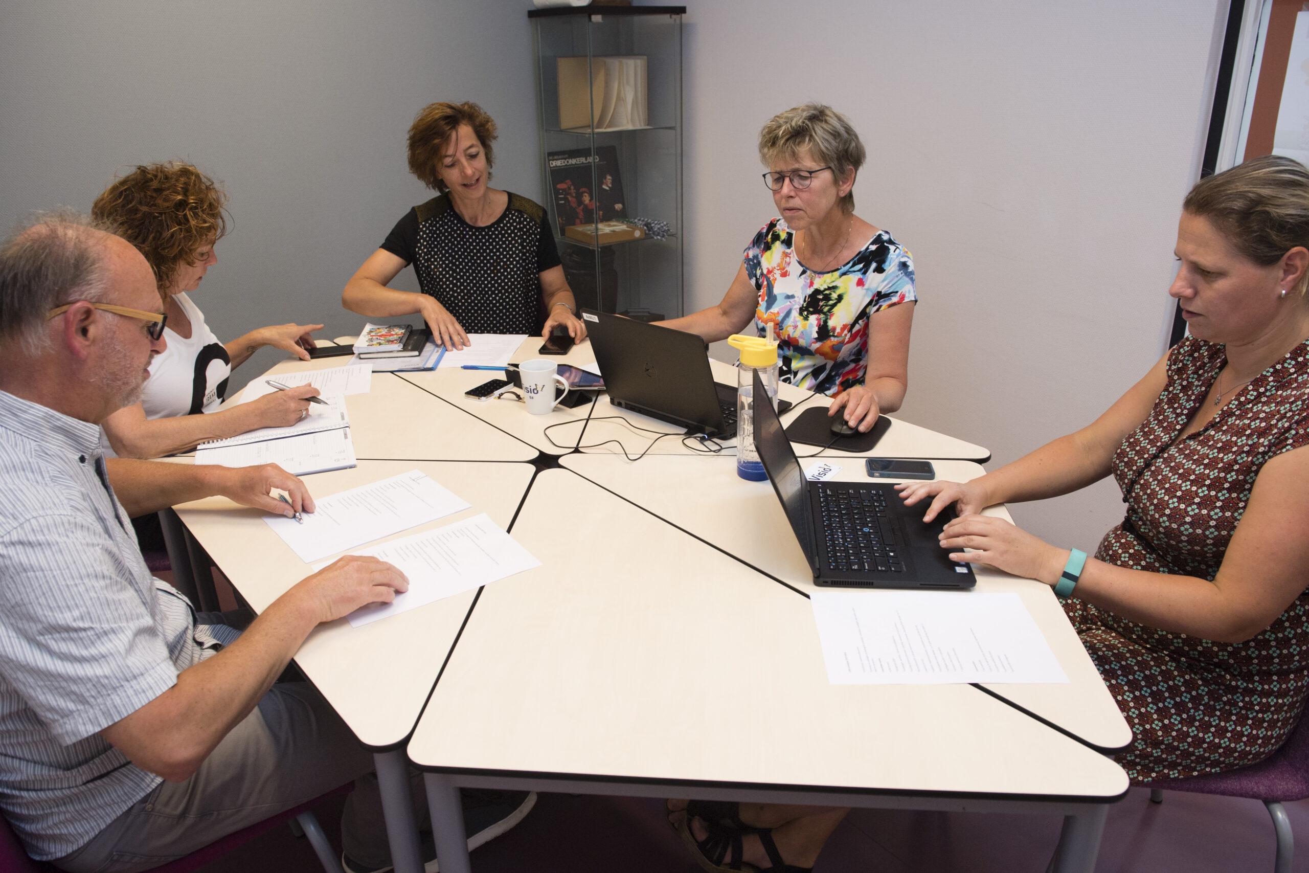 Docenten vergaderen over de onderwijslogistiek binnen het mbo.
