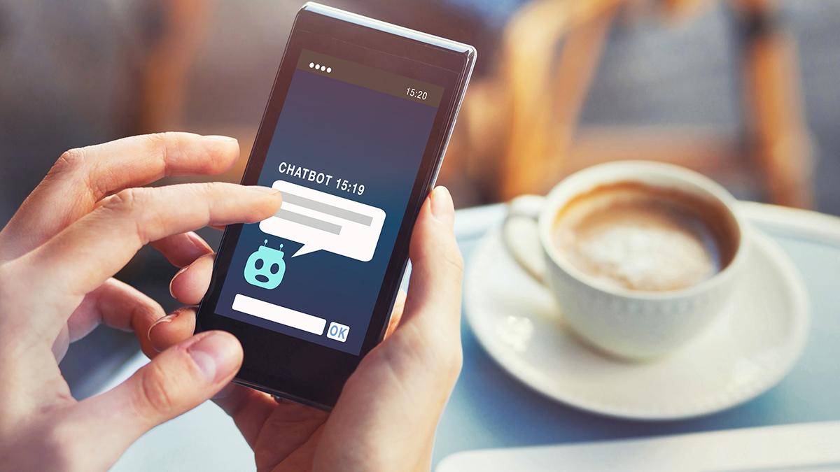 Een telefoonscherm in beeld waarop een gesprek met een chatbot zichtbaar is. Op de achtergrond staat een kop koffie.