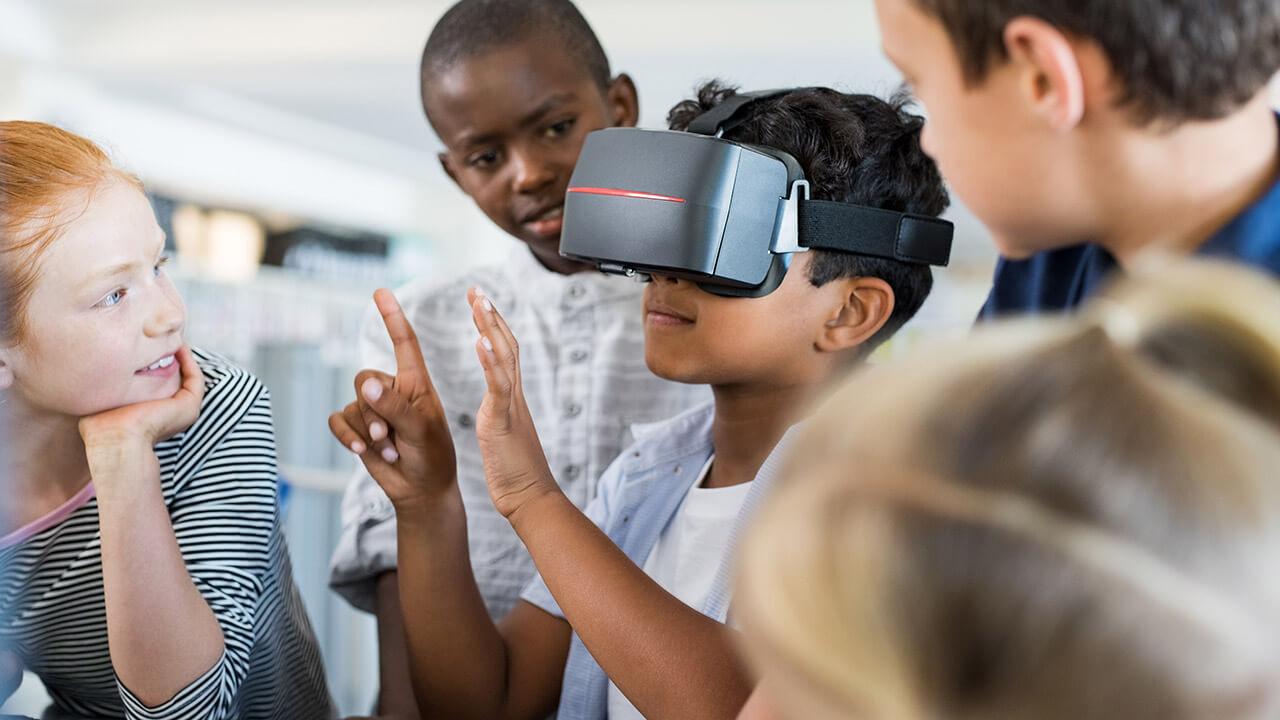 Een licht getinte leerling heeft een VR-bril op en vier andere leerlingen, zowel meisjes als jongens, staan om hem heen en kijken met belangstelling toe.