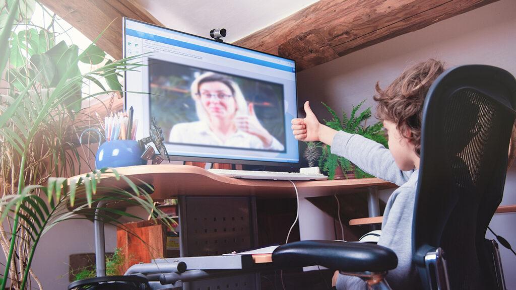 Een jongen zit op een stoel voor een groot beeldscherm en steekt zijn duim op naar het scherm. Op het scherm is een vrouw te zien die ook haar duim opsteekt.