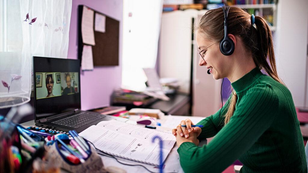 Een meisje zit achter haar laptop. Voor haar op tafel liggen werkboeken. Zij heeft een koptelefoon op. Op het scherm zijn twee personen te zien.