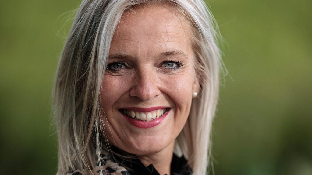 Marieke van den Berg, een blonde vrouw, kijkt lachend in de camera.