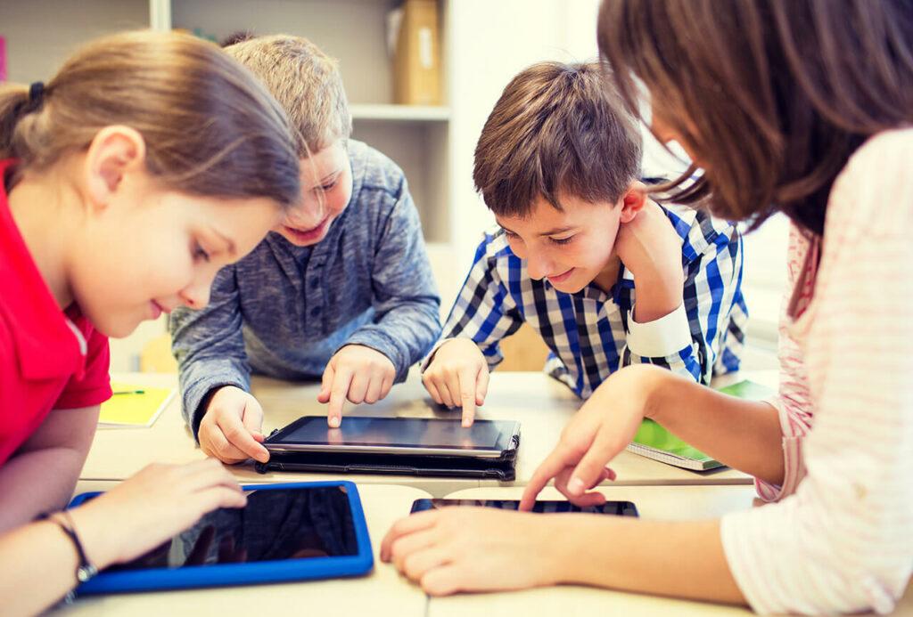 Vier jonge leerlingen hangen op een tafel en kijken ieder op een tablet