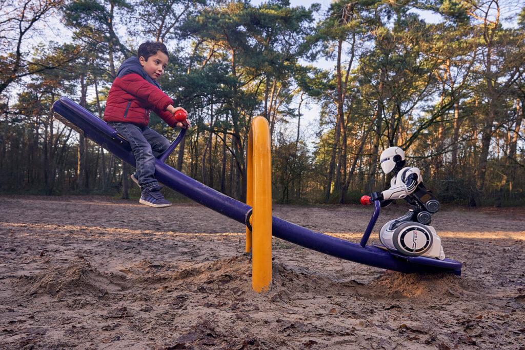 Een jongetje zit op een paarse wit. Tegenover hem zit een robot op de wip.