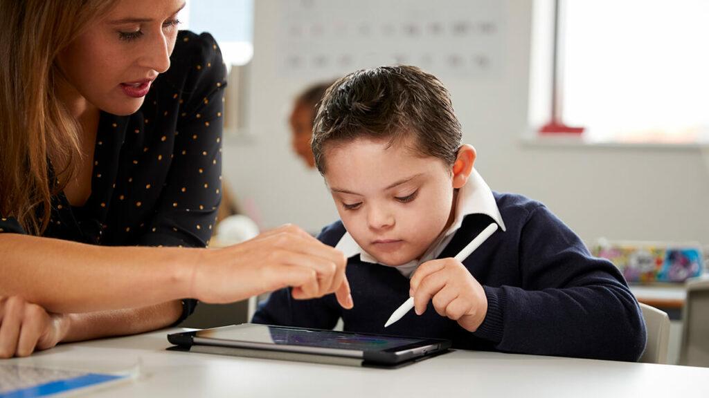 Een leerling met het Down Syndroom kijkt op een tablet en heeft een pen vast. Naast hem zit een lerares die met haar vinger boven de tablet hangt.