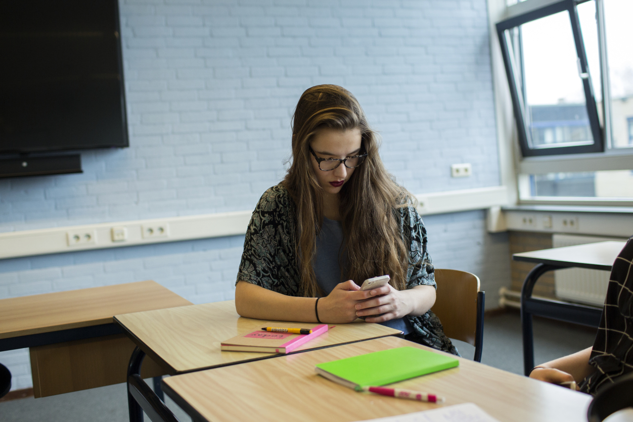 Een leerlinge in de klas die op haar mobiel een document digitaal ondertekend